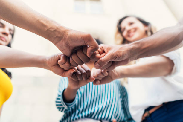 Unity Group of multi-ethnic young people stacking hands together unity stock pictures, royalty-free photos & images