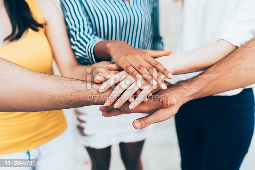 Group of multi-ethnic young people stacking hands together