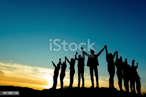 people silhouettes at sunset holding arms raised.