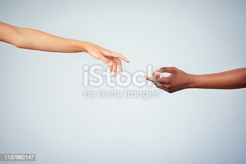 Cropped studio shot of two women joining their hands against a gray background