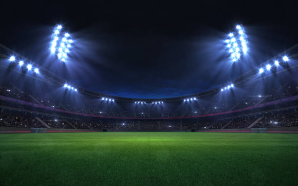 universal grass stadium illuminated by spotlights and empty green grass playground stock photo