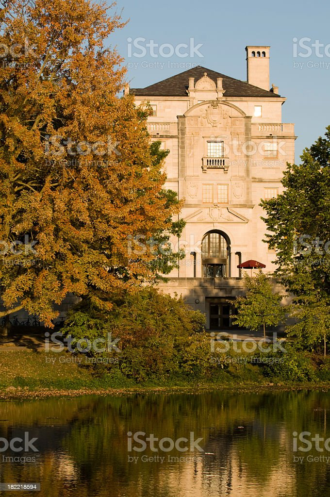 University building reflected in a pond on a sunny Fall day royalty-free stock photo