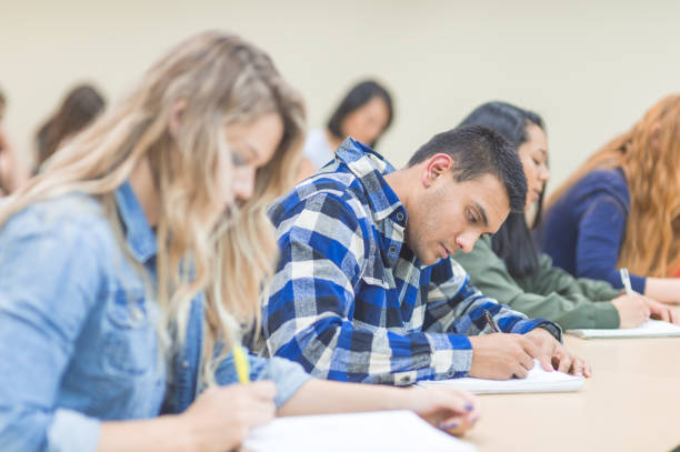 University Classroom Students in university lecture hall study together. They are writing and taking notes intently. A Caucasian female and male are in the foreground. adult learning stock pictures, royalty-free photos & images