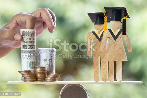 istock University Education learning abroad international Idea. Student Graduation save coins US dollar,JPY on wood round box balance. Concept of study requires money cost saving for success. Back to School 1151327427