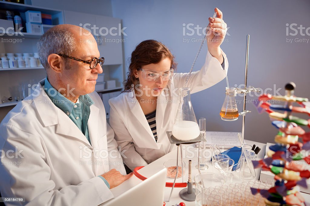 Chemistry science student in a laboratory with her teacher working on...