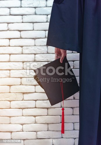 istock University graduate was holding his hat proudly. 1015232438