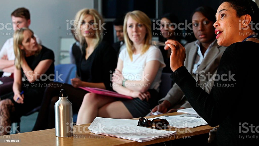 University lecturer advising students in class stock photo