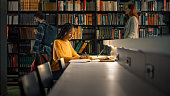 istock University Library: Gifted Black Girl uses Laptop, Writes Notes for the Paper, Essay, Study for Class Assignment. Students Learning, Studying for Exams College. Side View Portrait with Bookshelves 1248521772