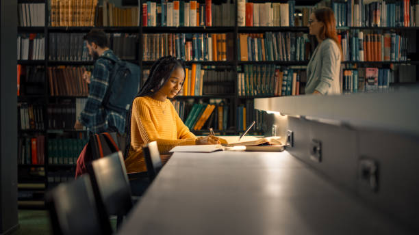 University Library: Gifted Black Girl uses Laptop, Writes Notes for the Paper, Essay, Study for Class Assignment. Students Learning, Studying for Exams College. Side View Portrait with Bookshelves stock photo