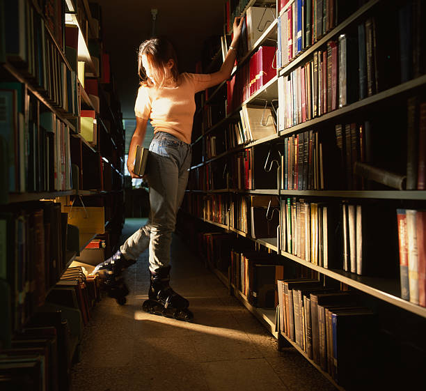 University Library Blond rollerblader among the books grifare stock pictures, royalty-free photos & images