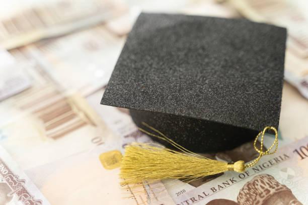 University Mortarboard academic cap on Nigerian Naira notes stock photo