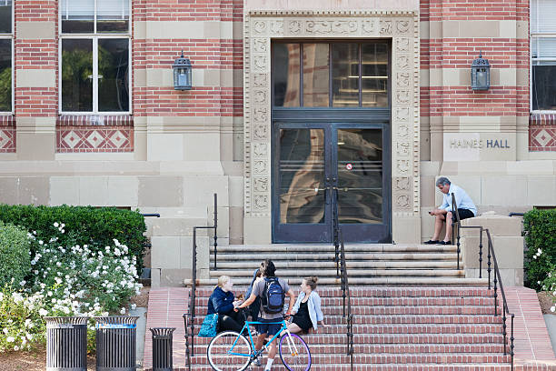 University of California, Los Angeles Los Angeles, California, USA - June 13, 2012. The location is University of California, Los Angeles. Groups of students sitting on the steps on the front of the building. One of the student is resting against a bike. ucla stock pictures, royalty-free photos & images