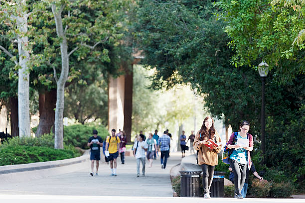 University of California, Los Angeles Los Angeles, California, USA - June 13, 2012. The location is University of California, Los Angeles. Two Asian female students are walking in the foreground. A larger group of students are walking in the background. ucla stock pictures, royalty-free photos & images