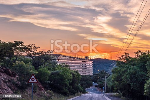 UNISA university building at sunset with the Freedom Park, a National heritage monument with the pillars representing reeds and the sunsetting above on the hill, in Pretoria, South Africa