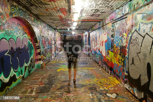 A hooded man walks through the Graffiti Tunnel at the University of Sydney at night. A designated graffiti site for students of the university, colourful designs adorn the floor, surface and ceilings.
