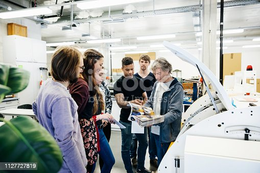 A university print technician giving a tour of the lab to a group of students.