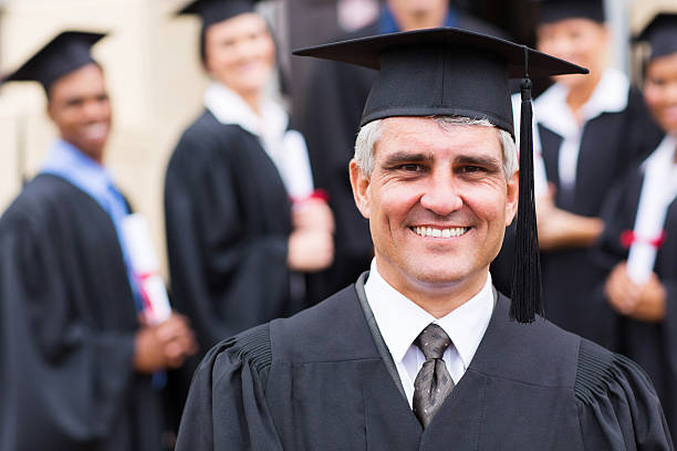 university professor in front of group of graduates handsome senior university professor in front of graduates college dean stock pictures, royalty-free photos & images