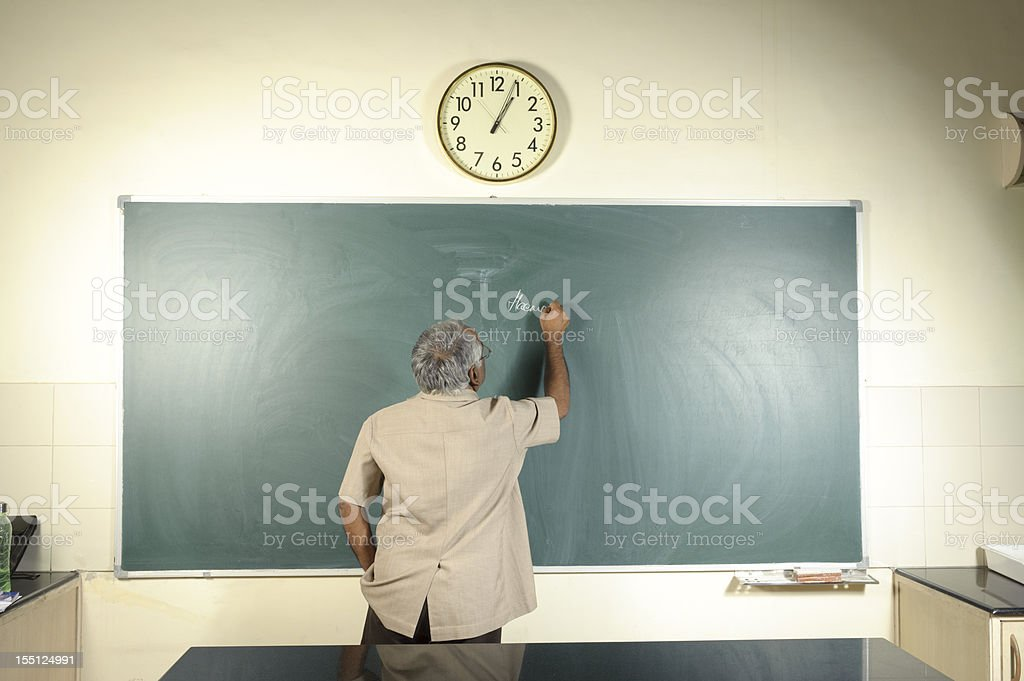 University Professor Writing on Blackboard stock photo