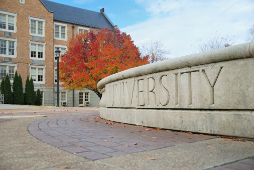 University sign in autumn with copy space