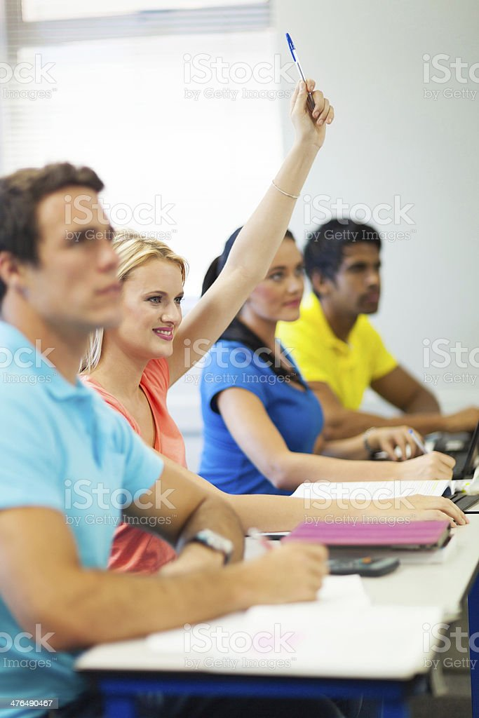 university student asking questing in lecture room stock photo