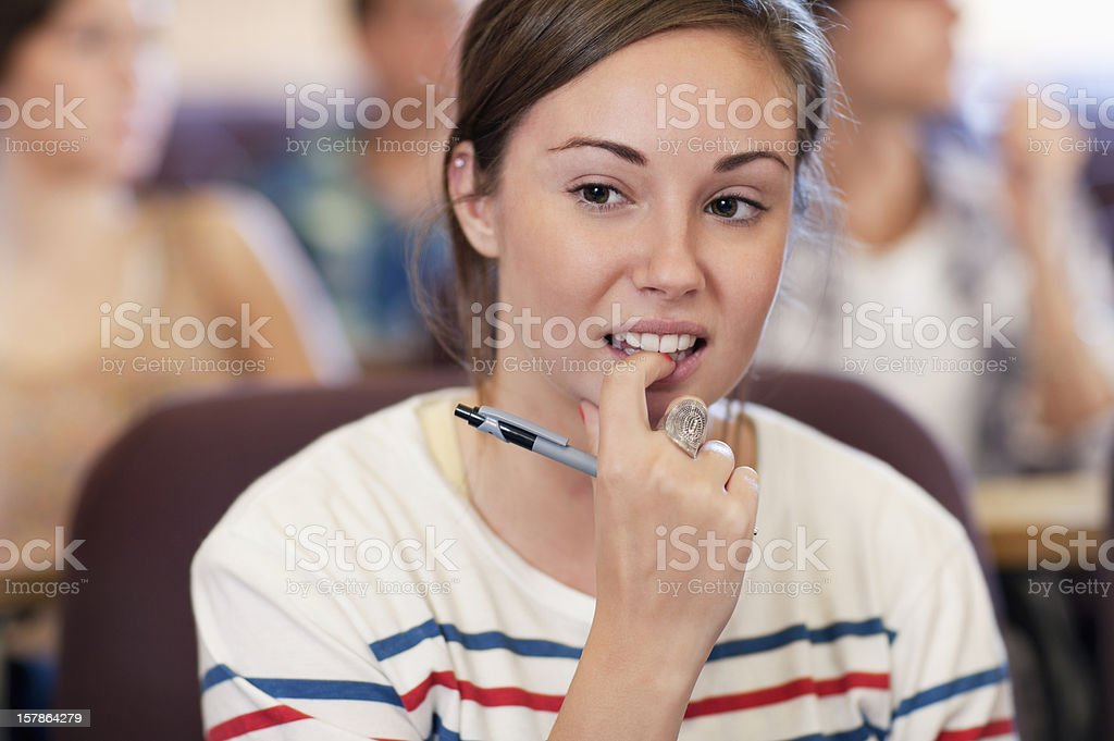 University student biting fingernail in lecture hall stock photo