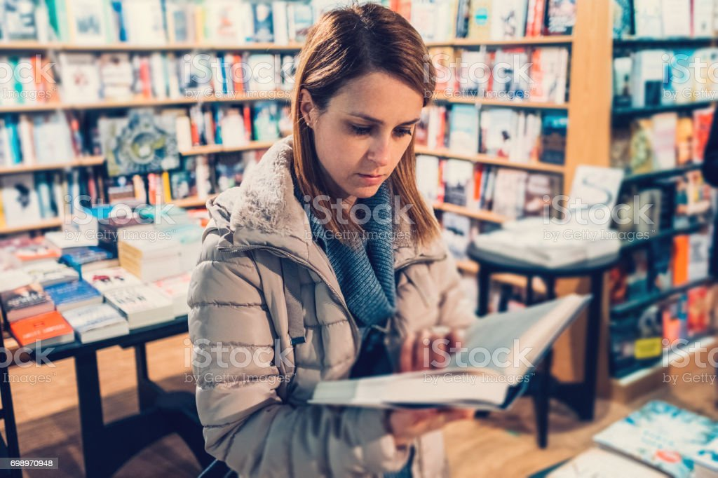 University student in the bookstore reading a book stock photo