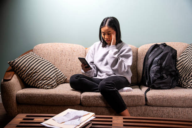 A university student of Asian heritage experiencing financial or emotional stress at home in her apartment. stock photo
