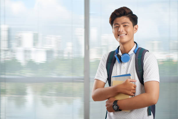 University student Happy Vietnamese student with books standing at big window vietnamese ethnicity stock pictures, royalty-free photos & images