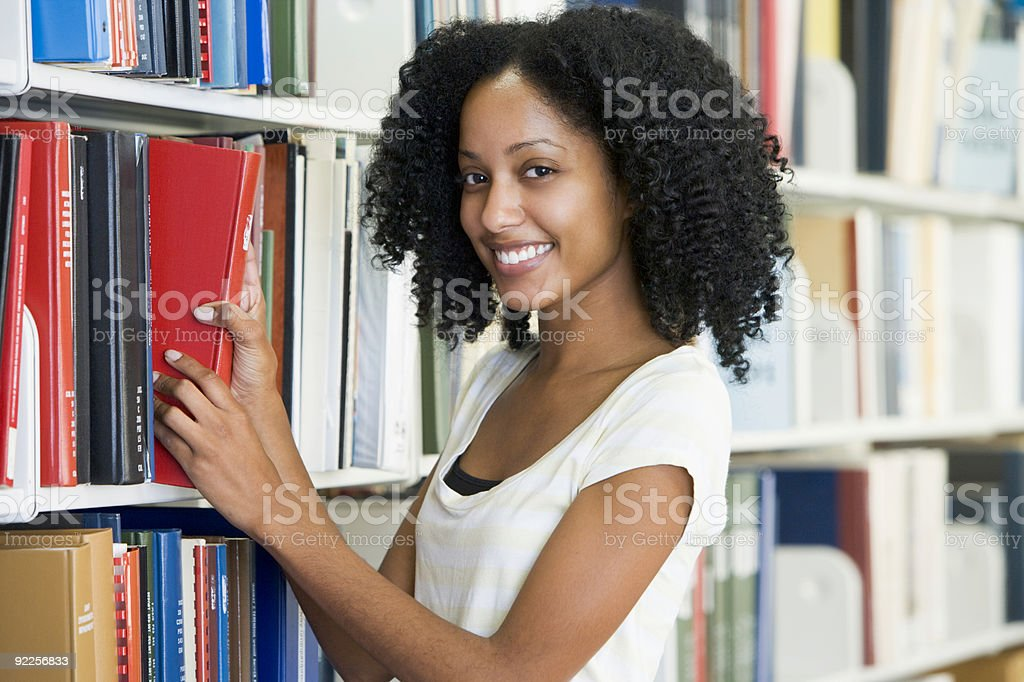 A university student selecting a book in a library royalty-free stock photo