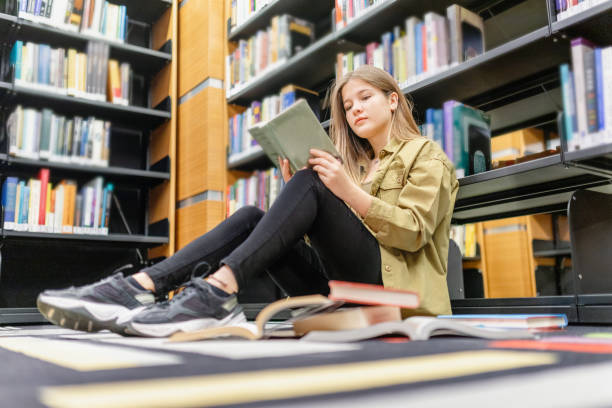 university student studying at library Young college student studying at library reference book stock pictures, royalty-free photos & images