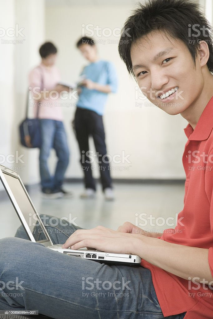 University student using laptop in hallway, friends in backgrounds foto royalty-free