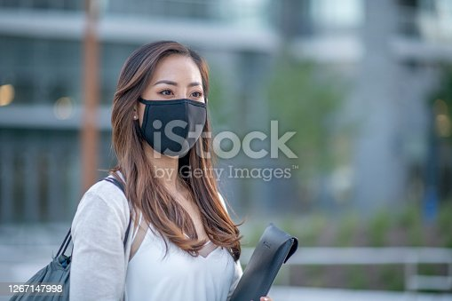 Asian female university student wearing protective face mask outside on campus.