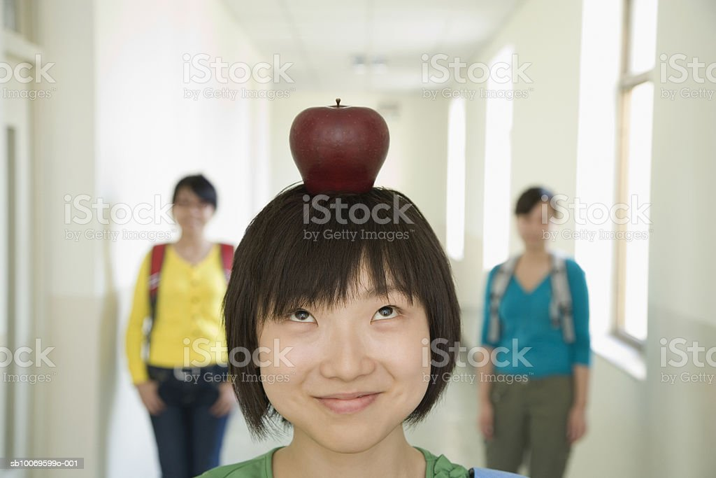 University student with apple on head standing in hallway, friends in backgrounds royalty-free 스톡 사진