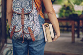 One woman, university student girl holding book, and wearing a backpack., rear view.