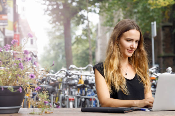 University Student With Laptop Outdoors stock photo