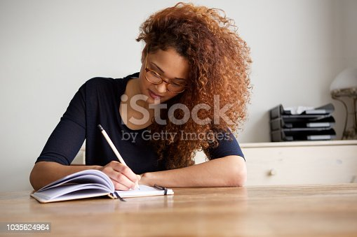 Portrait of university student writing in book at home