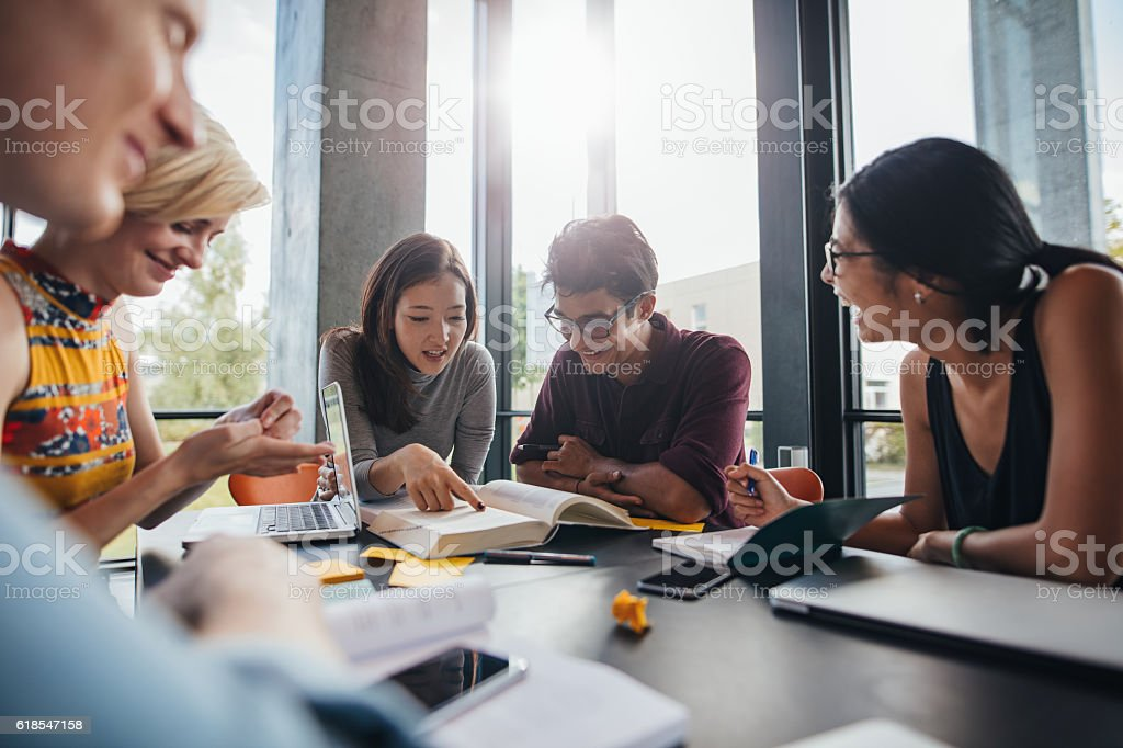 University students doing group study in library stock photo