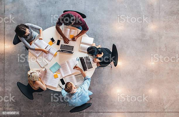 Top view of group of students sitting together at table. University students doing group study.