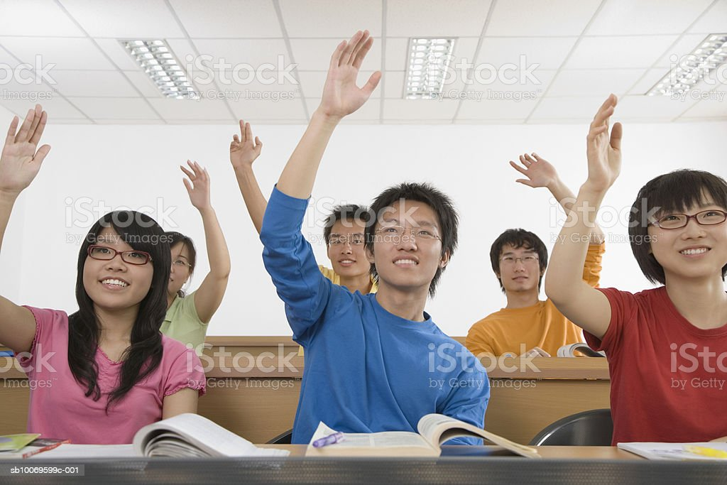 University students raising hands in classroom, smiling 免版稅 stock photo