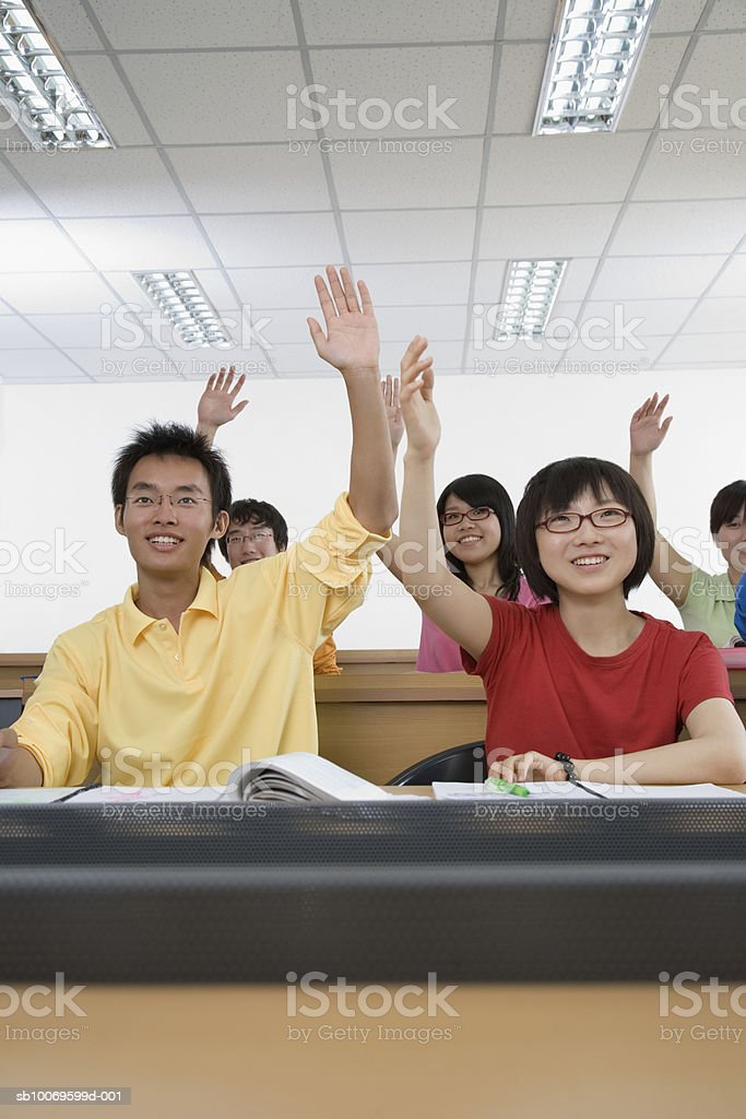 University students raising hands in classroom, smiling foto de stock royalty-free