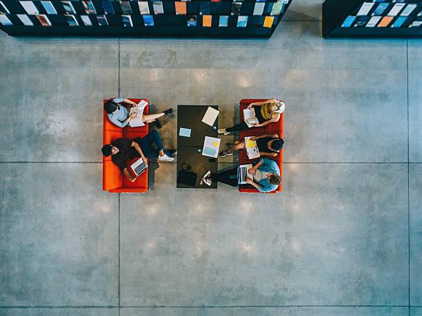 university students sitting in a library - consejero de la escuela fotografías e imágenes de stock