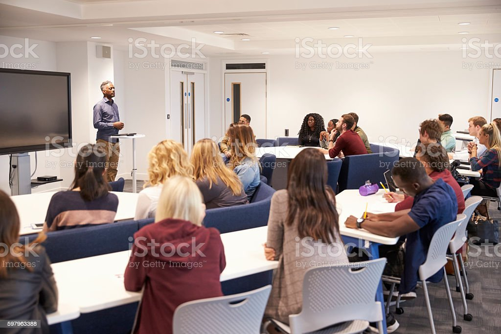 University students study in a classroom with male lecturer - foto de stock