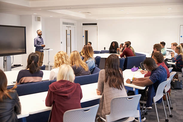 University students study in a classroom with male lecturer stock photo