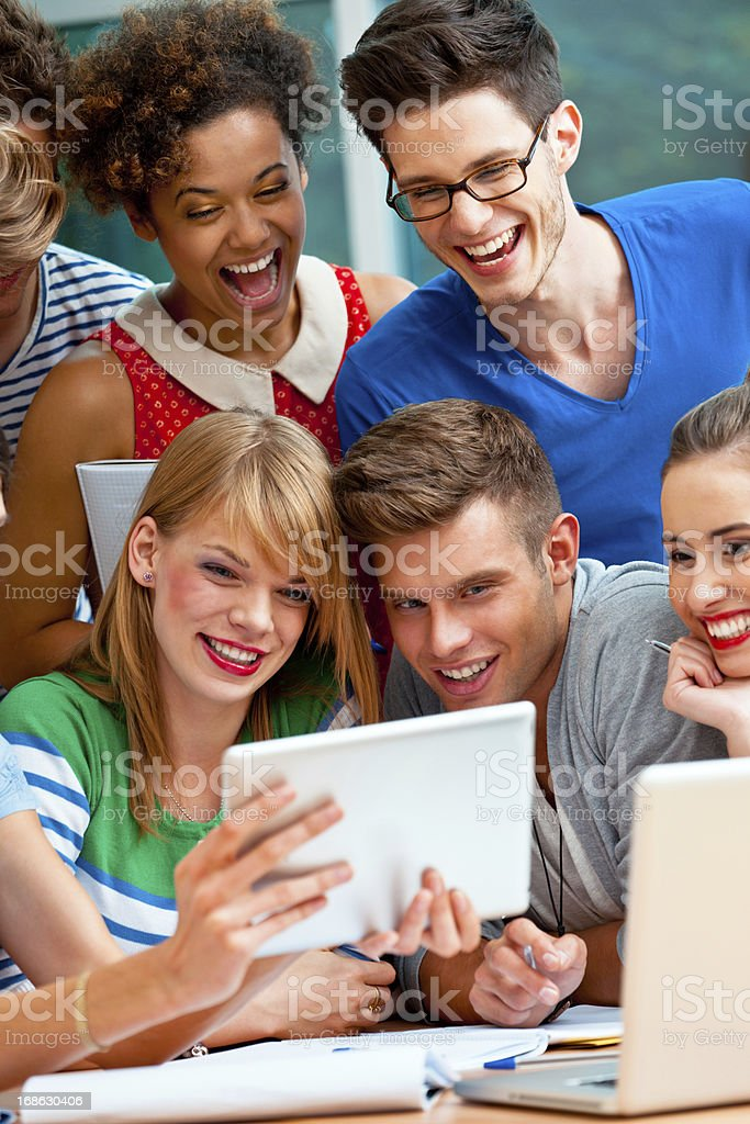 University students using a digital tablet Group of happy university students using a digital tablet together,  20-24 Years Stock Photo