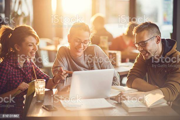 Group of young college students using laptop in a cafe.