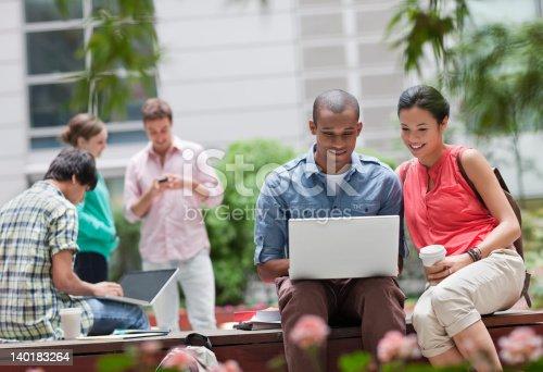 143071438istockphoto University students using laptop outdoors 140183264