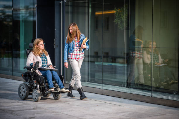 university students walking in campus - wheelchair stock photos and pictures