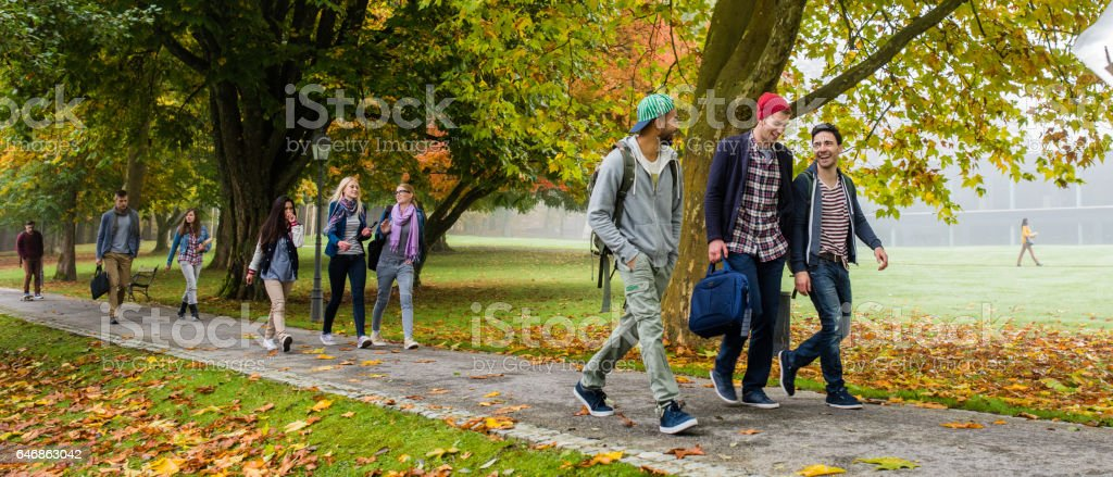 University students walking on footpath stock photo