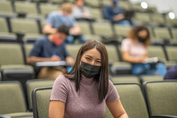 University students wearing masks in a lecture hall stock photo