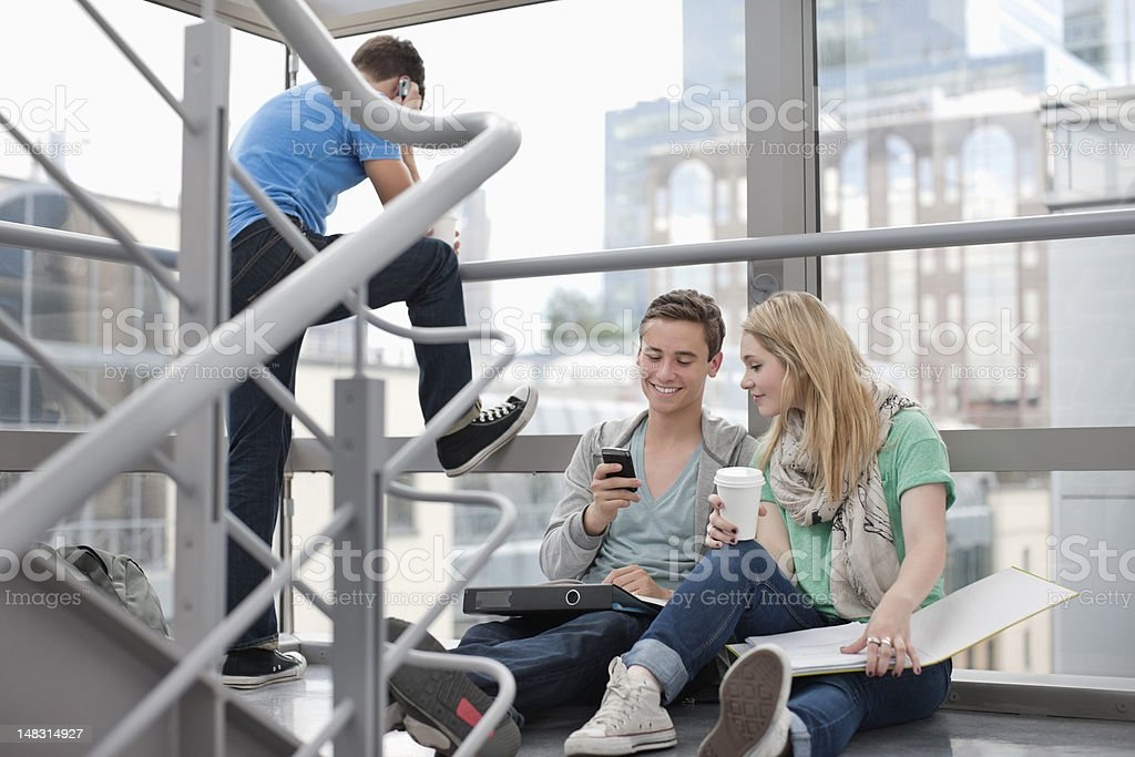 University students with binders and cell phone on stairs royalty-free stock photo